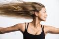 Awesome Caucasian attractive joyful happy female model is shaking head with blonde hair, wearing beige sport top