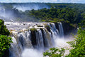 Awesome iguazu waterfall in brazil falls or iguassu falls beautiful cascade of waterfalls with clouds and jungle Royalty Free Stock Image