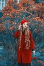 Awesome redhead woman in coat on flower background. Fashion model with long red hair with red flower in hand. Turban and stylish Royalty Free Stock Photo