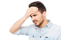 Awful headache frustrated young man in shirt touching forehead and looking away while standing against white background Royalty Free Stock Image