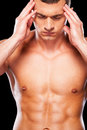 Awful headache young shirtless man touching head with hands and keeping eyes closed while standing against black background Stock Image