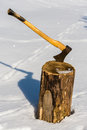 Ax stuck in wood log snow winter Royalty Free Stock Photo