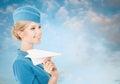 Azafata encantadora holding paper plane a disposición cielo azul backgr Imagen de archivo libre de regalías