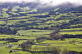 Azores green fields near povoação in são miguel island in low clouds on top of the mountains Royalty Free Stock Photo