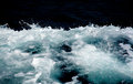 Azure and white boat wake seafoam with splashes sprays drops on dark blue background abstract Stock Photo