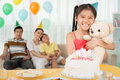 B day present portrait of a young girl with a teddy bear in hands on her birthday party on the foreground Stock Photos