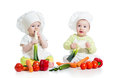 Babies boy and girl with healthy food vegetables children wearing chef hat Royalty Free Stock Photos