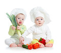Babies boy and girl with vegetables kids wearing a chef hat healthy food Royalty Free Stock Images