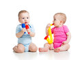 Babies girl and boy play musical toys playing on white background Stock Photo