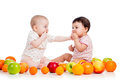 Babies girls eating healthy food fruits on white Royalty Free Stock Photography