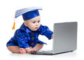 Baby in academic dress works on laptop Royalty Free Stock Photo