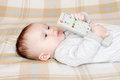 Baby age of months with remote control lovely Royalty Free Stock Images