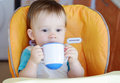 Baby age of year drink from baby cup sitting on chair Stock Photography
