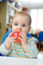 Baby with an apple at home vertical eating Stock Images