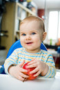 Baby with an apple at home vertical eating Royalty Free Stock Photo