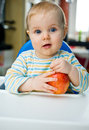 Baby with an apple at home vertical eating Royalty Free Stock Images