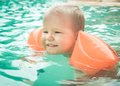 Cute toddler in swimming pool wearing red armbands