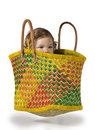 Baby in basket girl sits and hides inside a shopping Royalty Free Stock Photo