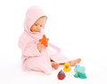 Baby in bathrobe playing with water rubber toys Stock Photo