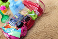 Baby beach bag with accessories on sand Stock Photos