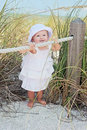 Baby at beach cute on wearing dress and hat Stock Image