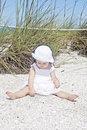 Baby at beach cute on wearing hat playing in sand Stock Photography