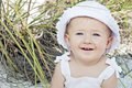 Baby at beach head and shoulders of cute on wearing hat Stock Photo