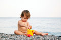 Baby on the beach playing with pebbles sitting and summer holiday Stock Photo