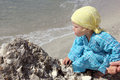 Baby on the beach toddler playing dressed with a blue dress and yellow bandana looking for seashells Royalty Free Stock Photos