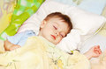Baby in bed ittle asleep his head on the pillow close up Stock Images