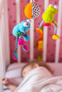 Baby bed with mobile toy above it