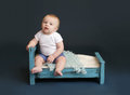 Baby bed time sitting in looking at camera against a dark blue background nap sleeping concept Stock Images