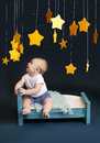 Baby bed time with stars and mobile sitting in looking up against a dark blue background nap sleeping concept Royalty Free Stock Photo