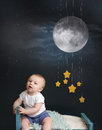 Baby bed time with stars moon and mobile sitting in looking at the starry night nap sleeping concept Stock Photo