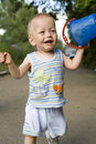 Baby blond boy with bucket outdoors Stock Image
