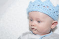 Baby with blue crown boy eyes wide open up close on his back wearing Royalty Free Stock Photo