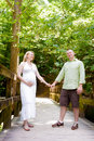 Baby on board happy young couple expecting a out for a walk holding hands a wooden bridge Royalty Free Stock Images