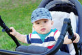 Baby boy age of months on buggy carriage in summer Royalty Free Stock Photo
