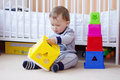 Baby boy age of year plays nesting blocks at home Stock Photo