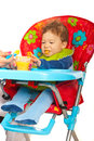 Baby boy being feeding by mother sitting in chair and his with puree Stock Photography