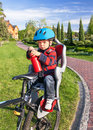 Baby boy is in the bicycle chair seat protection on caucasian with a biking helmet on his head and bottle of water Stock Photo
