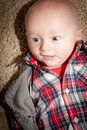 Baby boy with big blue eyes wide open looking to the side wearing a plaid shirt and vest Royalty Free Stock Image