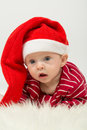 Baby boy with big eyes and with his mouth open in santa claus cap Stock Image