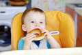 Baby boy biting round cracknel happy age of year eating on kitchen Stock Images