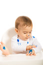 Baby boy with blue paint on hands paints his body sitting in a chiar isolated white background Stock Image