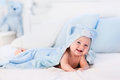 Baby boy in blue towel on white bed Royalty Free Stock Photo