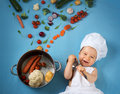 Baby boy in chef hat with cooking pan and vegetables Royalty Free Stock Photo