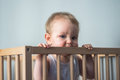 Baby boy chewing the crib`s wooden edge Royalty Free Stock Photo