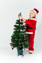 Baby boy dressed as santa claus decorating christmas tree hang hanging ornaments white background Royalty Free Stock Image