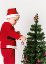 Baby boy dressed as Santa Claus decorating Christmas tree. Royalty Free Stock Photo
